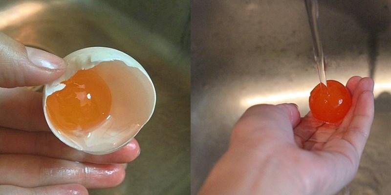 Xả lòng đỏ trứng muối dưới vòi nước