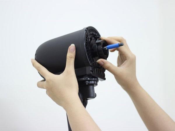 Tháo ốc bảo vệ khung quạt bằng cách vặn ngược chiều kim đồng hồ