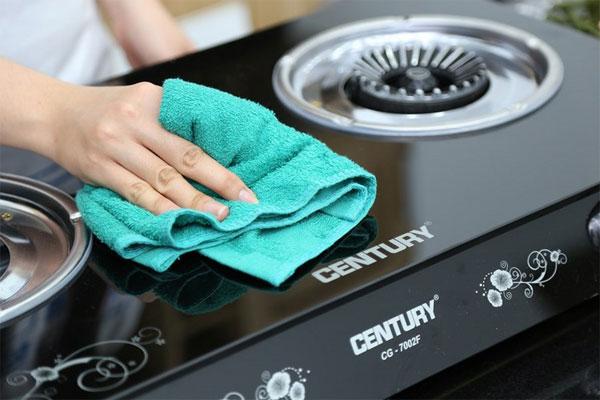 Dùng khăn lau chùi sạch mặt kính bếp