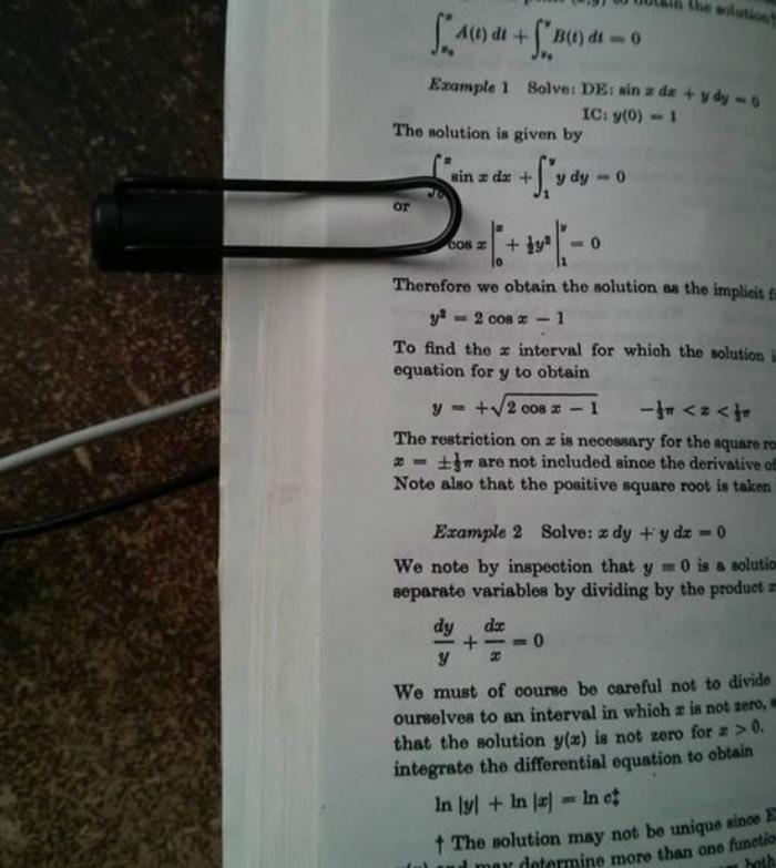 Dùng nắp bút bi kẹp giấy để sách không bị lật sang trang khác