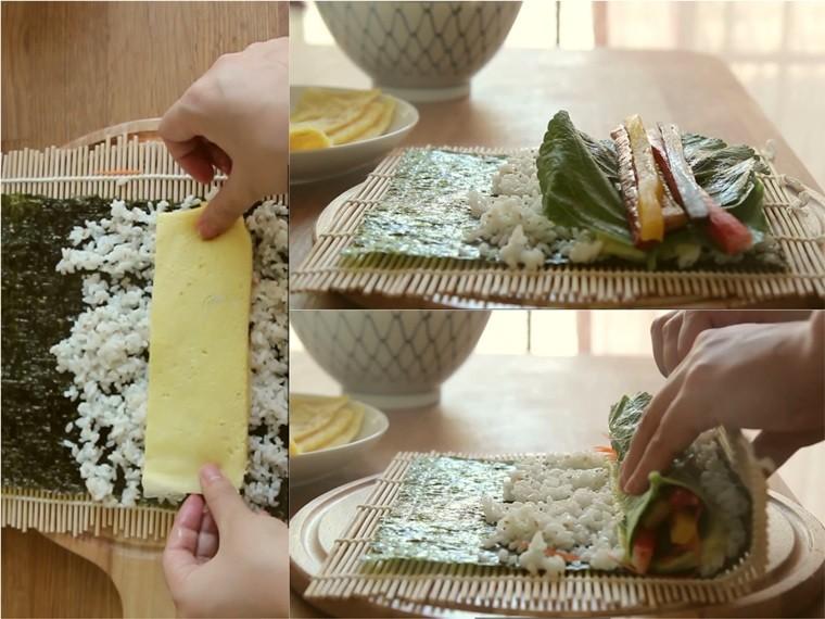 Bắt đầu cuộn kimbap, bạn đặt lá rong biển lên dụng cụ làm kimbap, sau đó rải cơm đều ra, đặt tiếp trứng, rau, cà rốt, thanh cua, chả cá, danmuji, pickled burdock, thịt nguội lên. Cuối cùng cuộn lại, nhớ đừng đặt quá nhiều nguyên liệu lên, khi cuộn kimbap của bạn có thể sẽ bị bể, rách, hỏng.