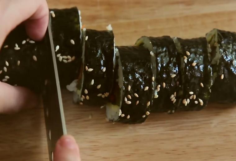 Cuộn xong, bạn rắc lên chút mè và quét ít dầu mè và cắt chúng thành những khoanh tròn như trong hình.