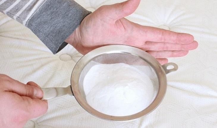Rắc bột baking soda lên bề mặt nệm và để khoảng 30 phút