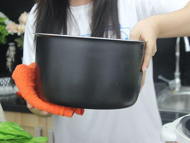 Lau khô mặt ngoài nồi con trước khi đặt vào mâm nhiệt