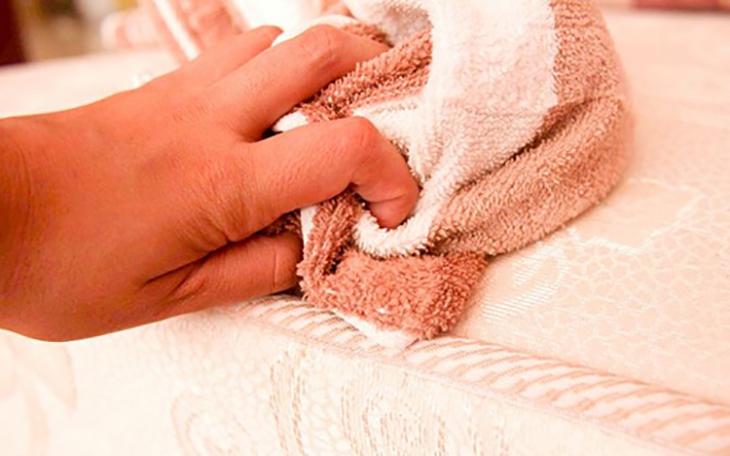 Dùng khăn lông thấm dung dịch xà phòng pha loãng để cọ sạch bề mặt nệm