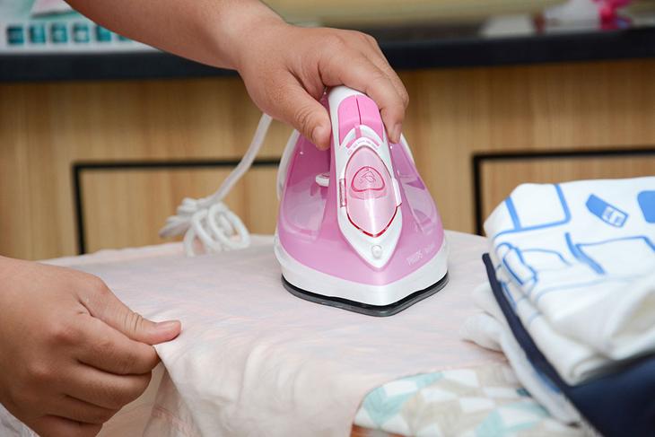 Tiến hành ủi quần áo