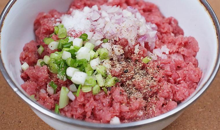 Ướp thịt băm với một ít muối, bột ngọt, tiêu, tỏi băm và hành băm rồi trộn đều.
