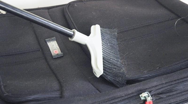 Làm sạch bụi bẩn bên ngoài vali với bàn chải mềm