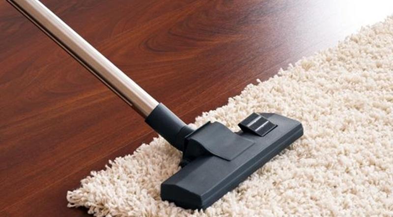Dùng máy hút bụi làm sạch vết bẩn trên thảm chùi chân