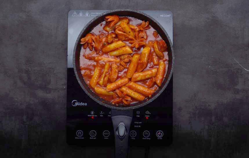 - Khi gà đã săn lại bạn cho bánh gạo vào đảo đều, thêm xúc xích và cho thêm 100 ml nước, nấu sôi 5 - 7 phút.