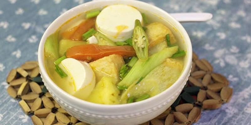 Canh chua chay có vị chua dịu của thơm và me, thêm đậu phụ non mềm mềm và nhiều rau thanh mát.