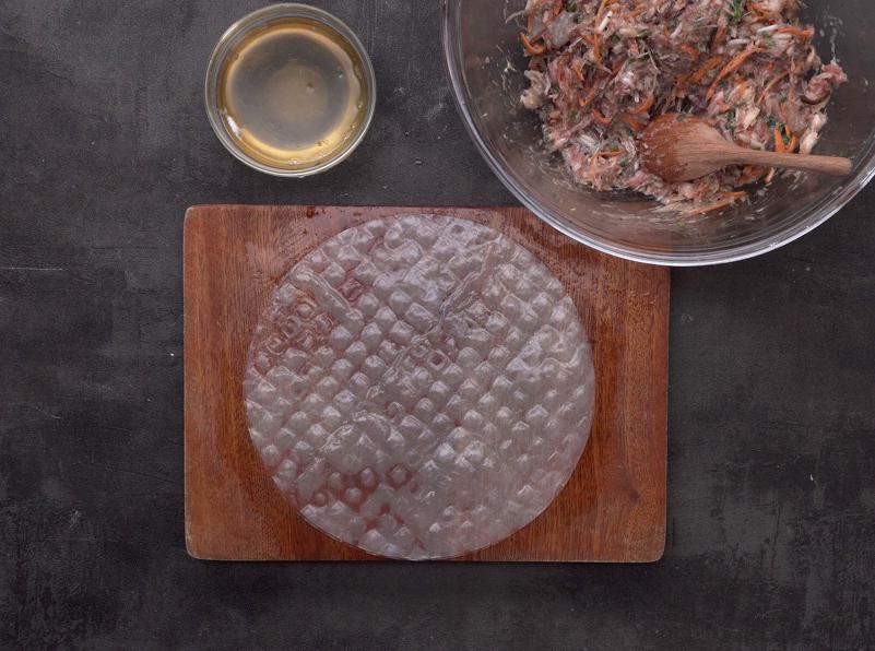 Lấy bánh tráng cuốn trải ra đĩa, làm ướt bánh tráng bằng cọ sạch nhúng bia rồi tiến hành gói nem.