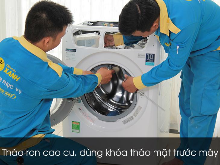 Dùng khóa tháo mặt trước máy ngay cửa lồng giặt