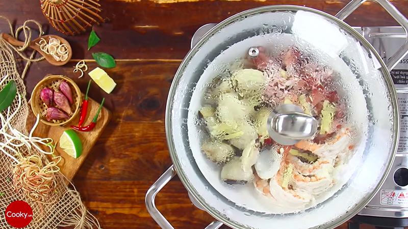 Cho các loại hải sản lên xửng hấp, để lên vài lát gừng cho thơm rồi đậy nắp hấp trong 10 phút cho chín.