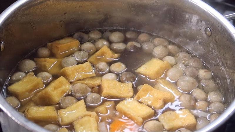 Phần nước dùng sau khi đã nấu được 40 phút, thì cho phần nấm rơm đã xào và đậu hủ chiên vào, nêm nếm với gia vị, nấu thêm 5 phút nữa thì tắt bếp.