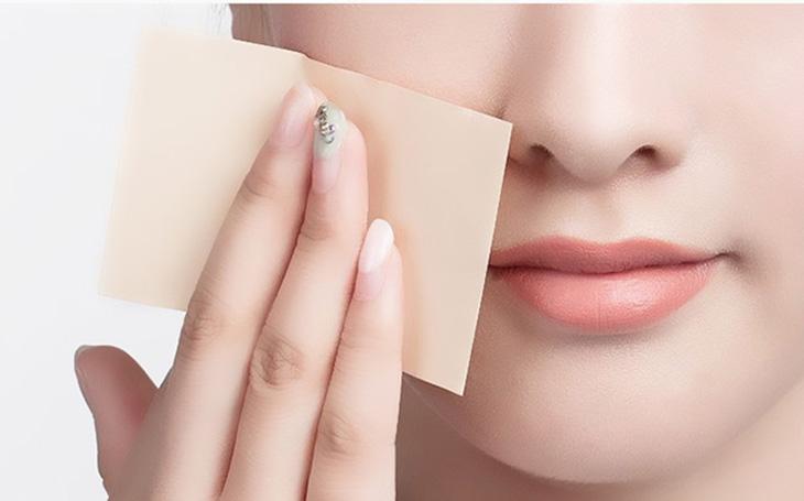 Sử dụng giấy thấm dầu giúp loại bỏ bóng nhờn trên da.