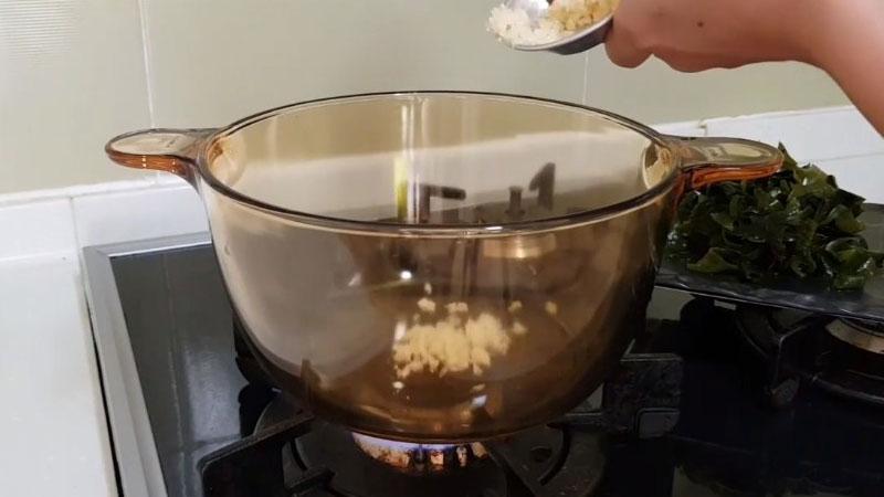 Cho dầu mè và 1/2 phần tỏi băm vào trong nồi, rồi dùng đũa đảo đều cho tỏi vàng thơm.
