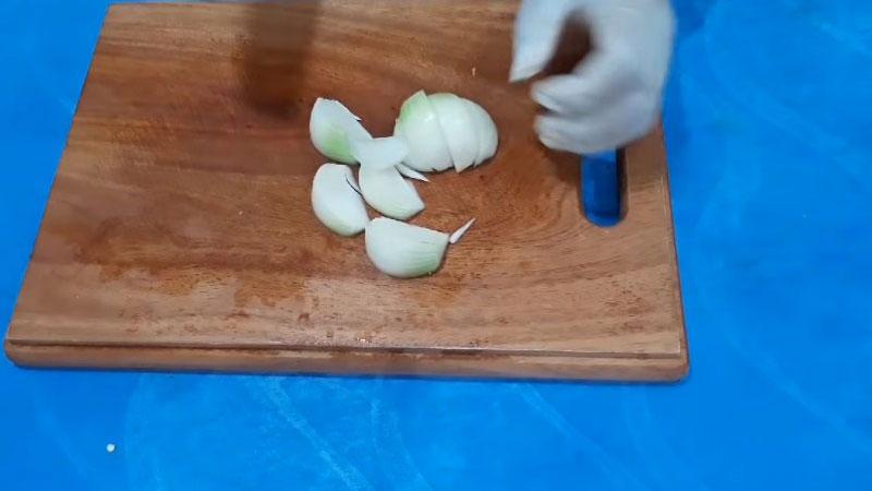 Hành tây lột vỏ, rửa sạch, cắt làm đôi rồi cắt múi cau.