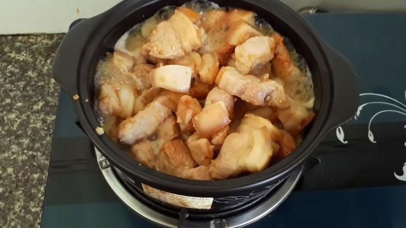 Sau đó cho nước vào xâm xấp mặt thịt, nấu đến khi nước sôi lên thì hạ nhỏ lửa, nêm nếm lại với gia vị cho vừa ăn, rồi kho thêm 15 phút.