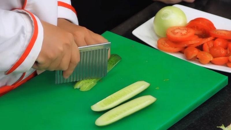 Dưa leo rửa sạch, cắt làm đôi để bỏ đi phần ruột bên trong, rồi cắt thành từng miếng xéo vừa ăn.