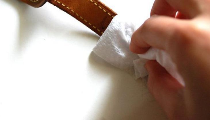 Dùng khăn mềm nhúng vào dung dịch đã pha và chùi nhẹ nhàng phần dây da
