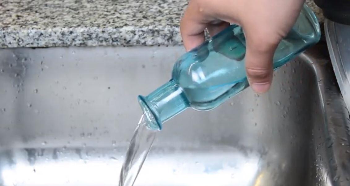 đổ hết nước trong chai ra ngoài