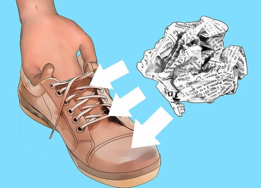Vo giấy báo thành hình tròn rồi nhét vào giày cho đến khi đầy.Vo giấy báo thành hình tròn rồi nhét vào giày cho đến khi đầy