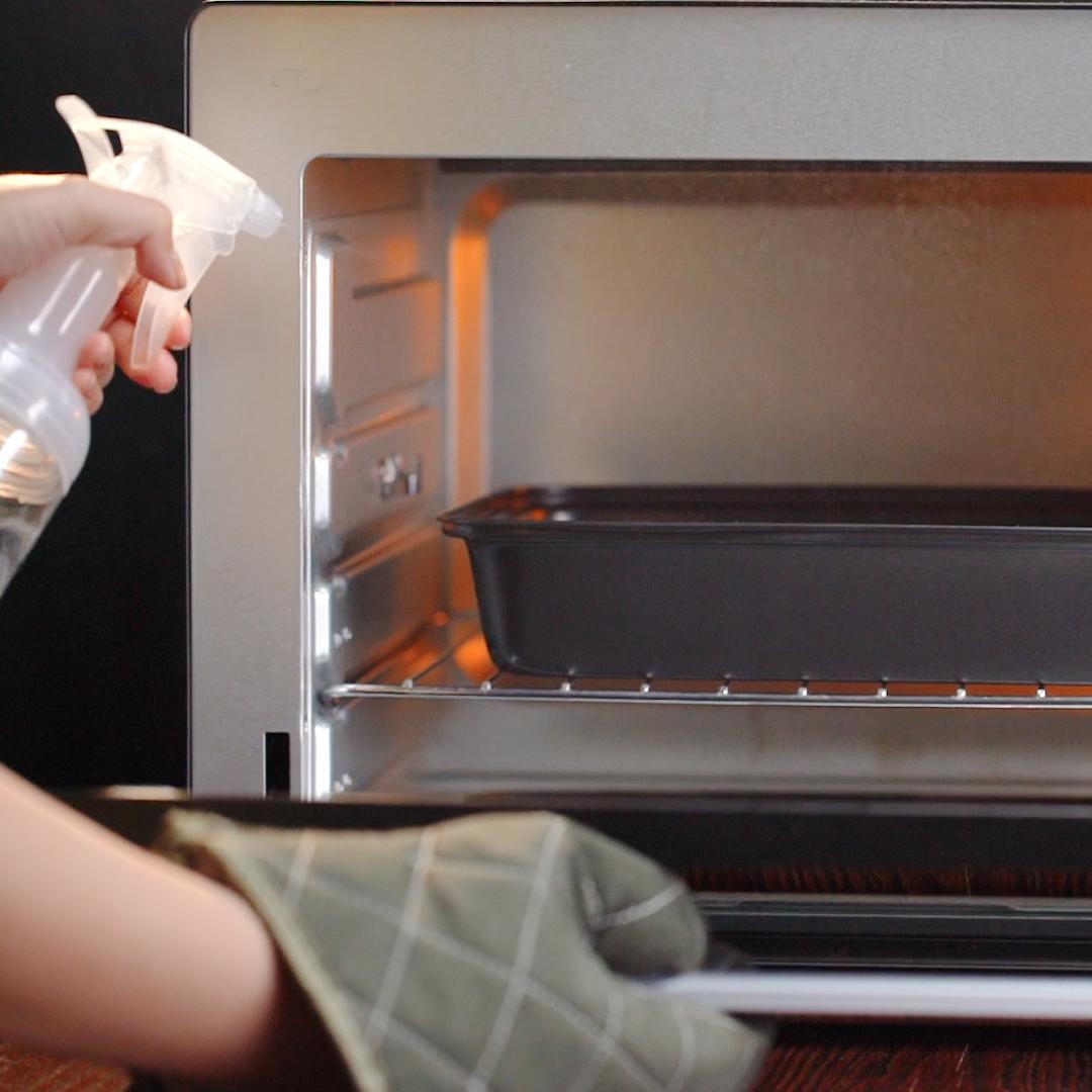 - Khi lò đã nóng, bạn đem bánh để vào lò nướng. Khi đã nướng được 5 phút bạn thấy mặt bánh đã khô thì mở lò xịt nhanh lên mặt bánh một ít nước nữa. Sau đó đóng lò và hạ xuống 200 độ.