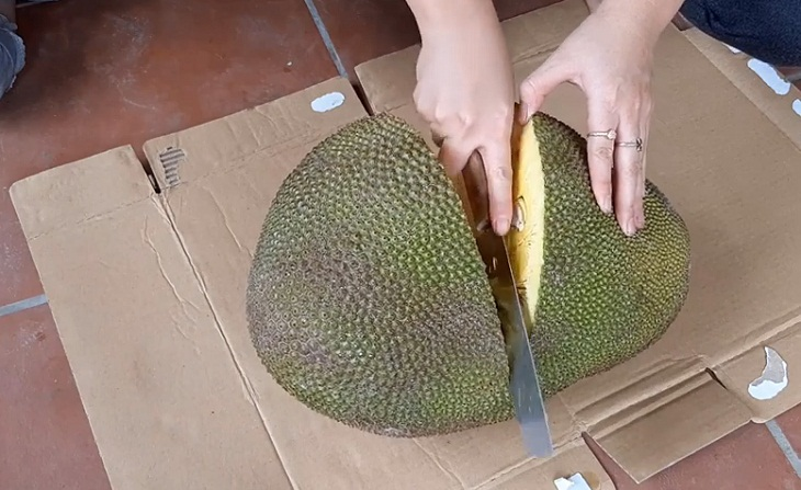 Đặt trái mít lên miếng bìa cứng (giấy báo), dùng dao bổ ngang đôi thân trái mít.