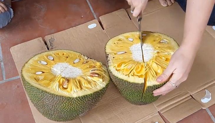 Tiếp tục bổ đôi mỗi nửa trái mít vừa mới cắt.