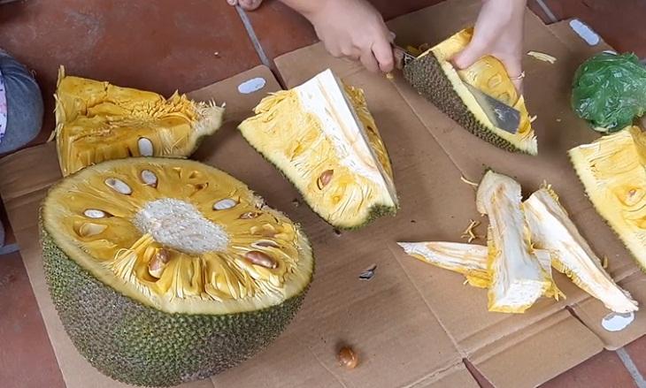 Dùng dao gọt vỏ bên ngoài của mít và tách ra từng múi để sử dụng, hoặc bảo quản trong hộp đựng thực phẩm trước khi dùng.