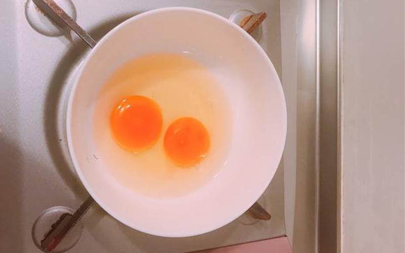 Cho 2 quả trứng vào tô và đánh đều
