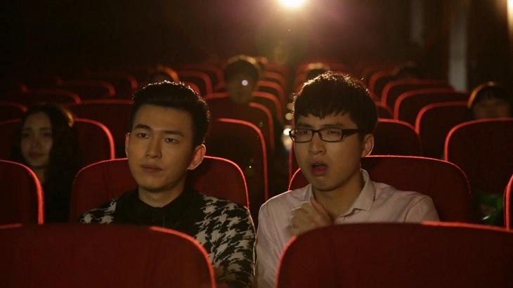 Hai nhân vật chính đang ngồi cùng nhau trong rạp chiếu phim