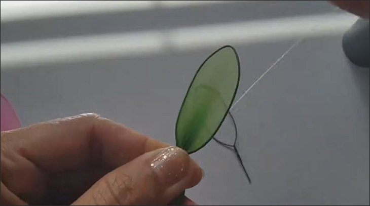 Dùng vải quấn chiếc vòng quanh khung kẽm, tương tự như trên và dùng chỉ cố định khung kẽm vào tấm vải. (Nguồn ảnh: Youtube HANDMADE TV)