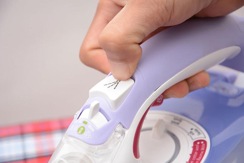 Nhấn nút phun tia để làm ẩm sợi vải