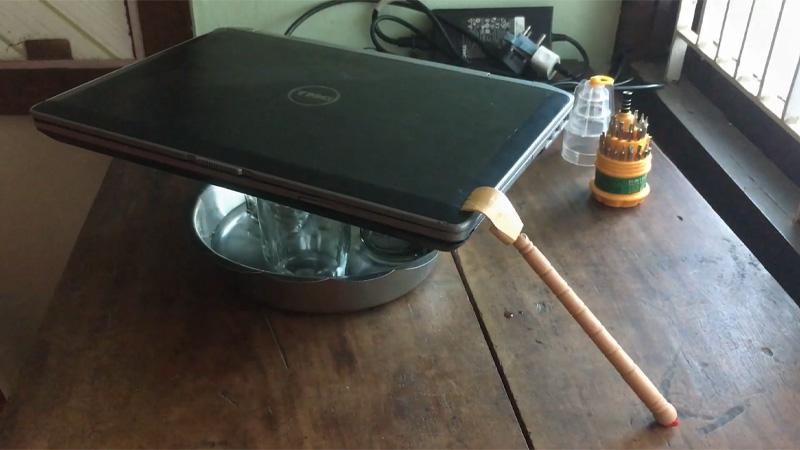 Đặt muỗng lên laptop và khay sao cho muỗng không bị rớt